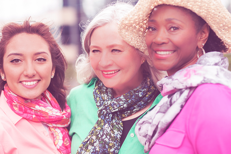 three smiling women in scarves