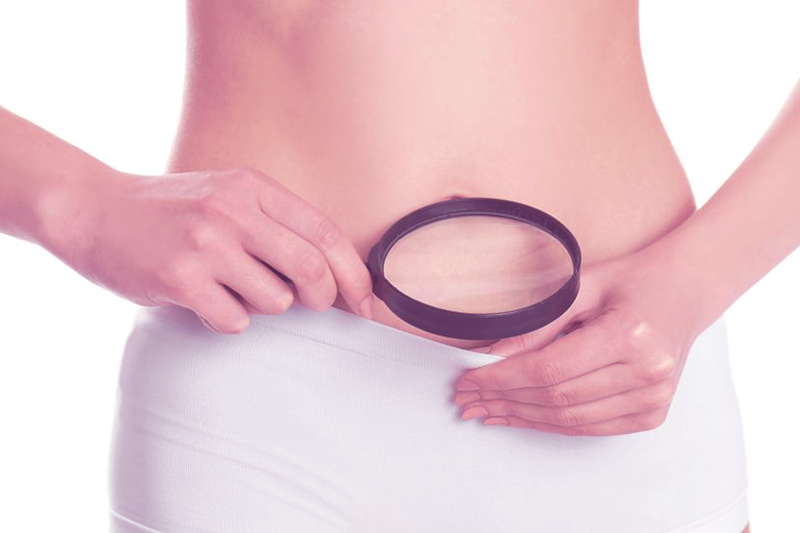 woman holding a magnifying glass to look at her vagina