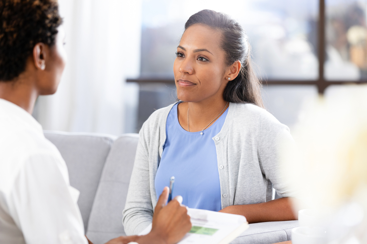 Mid adult woman talking to doctor